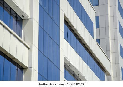 Modern architectural background of metal panels and blue glazing close up