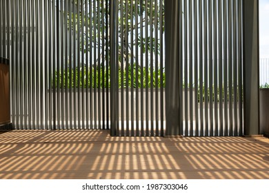 modern architectural shaded garden indoor outdoor area with vertical slats casting strong shadows on timer decking floor. A frangiapani tree can be seen through the screen.