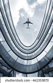 Modernes Architekturgebäude mit fliegendem Flugzeug im Hintergrund. Blaues Bild im unteren Winkel.