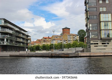 Modern architecture and a historic tower in Karlstad, Sweden, Scandinavia, Europe. On the banks of the river Klaralven are residential buildings with glazed loggias for each apartment.