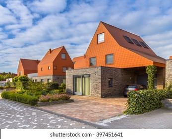 Modern architecture houses with remarkable red roof tiles in a contemporary suburban neighborhood in the Netherlands