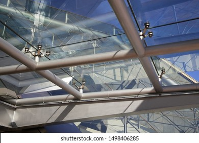 Modern architecture and interior design. Sky in a hi-tech building. Fragment of structural glazing. Transparent ceiling or roof of modern modular house featuring glass panels and steel girders.