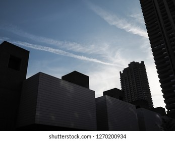 Modern architecture in London, UK, silhouetted against the evening sky with vapour trails