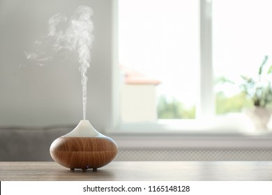 Modern aroma lamp on table against blurred background with space for text