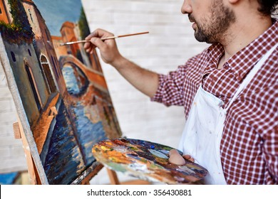 Modern artist painting landscape with oilpaints