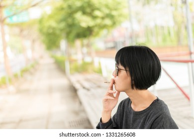 modern Asian beauty with glasses smoking at street in the city