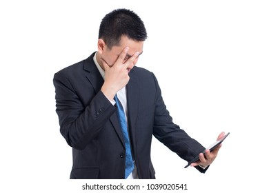 Modern asian businessman hand holding digital tablet suffering from headache on white background. Hiding he face and confused angry with unhappy. sad face and standing and thinking negative