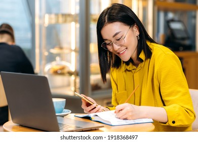 Modern Asian female student in stylish casual clothes, studying remotely using a laptop, listening to an online lesson, taking notes in a notebook, while sitting in a coffee shop. Online education