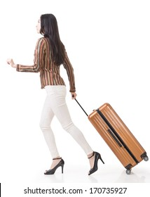 Modern Asian woman running and holding a suitcase, side view full length portrait isolated on white background.