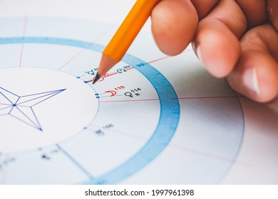 Modern astrologer's desktop. Hand with a pencil. Astrological charts and tables with the coordinates of the planets, astrological symbols close-up.