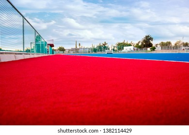 A modern astroturf / artificial grass hockey field in red and blue