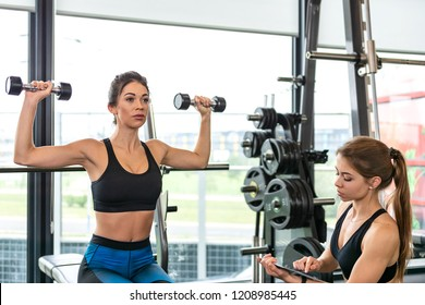Modern athletic workout concept - fitness woman is training with dumbbells at the gym and is leading by a trainer and an application on a tablet.
