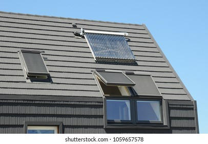 Modern attic roof with solar panels, skylights and blinds window for sun protection and house energy efficiency.