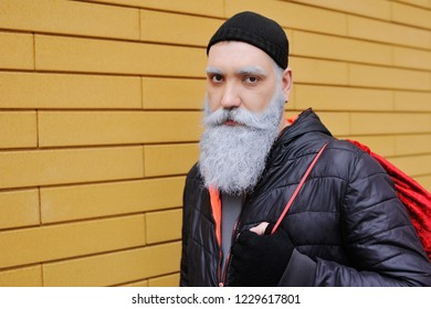modern attractive Santa Claus with a beautiful gray-haired beard with a red bag with gifts on a yellow brick wall background. Copy space