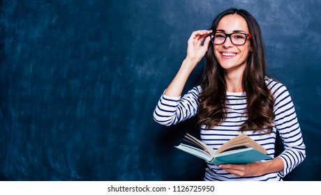 Modern attractive teacher. Portrait of Beautiful smart young woman in glasses with book isolated on the gray background. Study concept