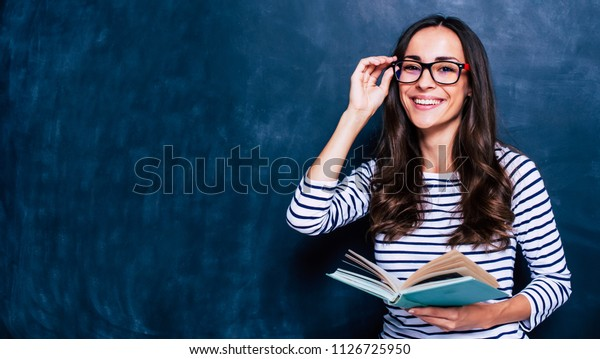 Profesor moderno y atractivo. Retrato de bella joven inteligente en gafas con libro aislado en el fondo gris. Concepto de estudio