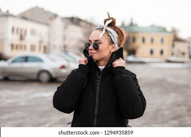 Modern attractive young hipster woman in winter stylish clothes with a hairdress with a bandana in sunglasses in the city on the background of vintage buildings. Stylish american girl travels.