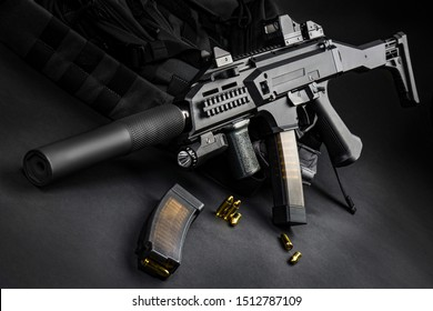Modern automatic rifle with a silencer and a collimator sight on a dark background. Tactical submachine gun. Weapons for the police and special units. Studio shot.