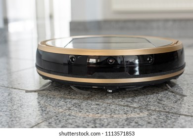 Modern autonomous robotic vacuum cleaner on bright marble floor with reflections - modern and convenient smart cleaning technology. Space for your copy text on bright background