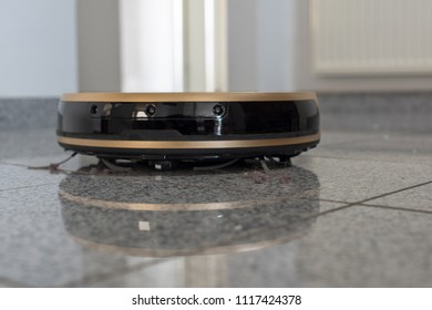 Modern autonomous robotic vacuum cleaner on bright marble floor with reflections. Focus on hairs and dust. with sace for your copy text on bright background