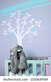 Modern baby room design with a cot, stuffed elephant toy and tree wall mural