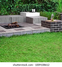 Modern Backyard Party Or Family Area With Open Iron Fireplace And Stationary Furniture Made From Bricks, Wood And Tiles. Garden Landscaping Concept And Idea