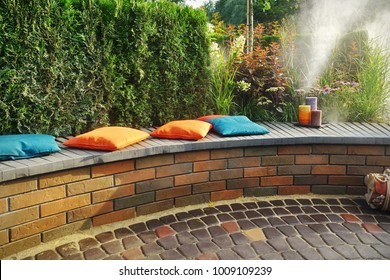 Modern Backyard Patio And Party Area On Backyard Garden. Family Corner For Relaxation And Rest On Wooden And Brick Rounded Bench With Pillows