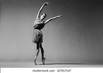 Modern ballerina in short dress posing on toes, studio background. Grayscale image.