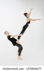 Modern Ballet Couple do Dance High Level Lift. Man in Demi Plie, Woman Dancer Stand on his Hip do Arabesque. Young Perfomer in Black Form do Sensual Movement Isolated on White Background