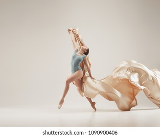 Modern ballet dancer exercising in full body on white studio background. Ballerina or female dancer with silk fabric dancing on white studio background. Caucasian model on pointe shoes