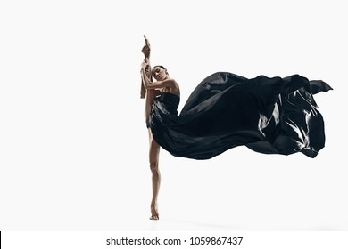 Modern ballet dancer exercising isolated in full body on white studio background. Ballerina or modern dancer in black silk dress dancing on white studio background. Caucasian model dancing barefoot