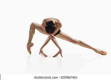 Modern ballet dancer exercising isolated in full body on white studio background. Ballerina or modern dancer in black swimsuit dancing on white studio background. Caucasian model on ballet pointe
