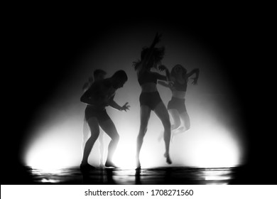 modern ballet dancers jumping and dancing. motion blur and smoke in the air