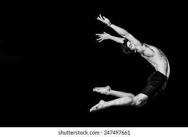 Modern ballet style male dancer performs on high lighted stage black and white