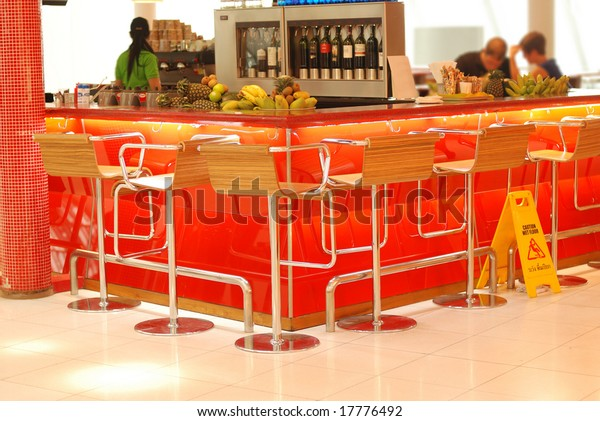 Modern bar in airport. No recognizable faces or brandnames.