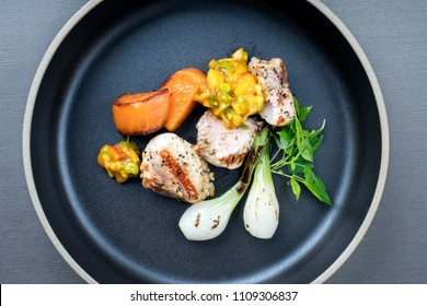 Modern barbecue crocodile tail eye fillet with roasted sweet potatoes and mango chili chutney as top view on a plate