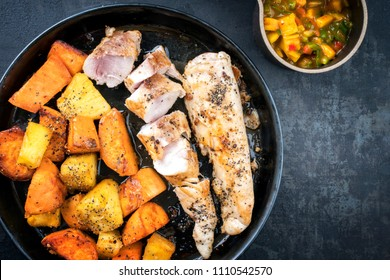 Modern barbecue crocodile tail eye fillet with roasted sweet potatoes pineapples and mango chili chutney as top view on a plate