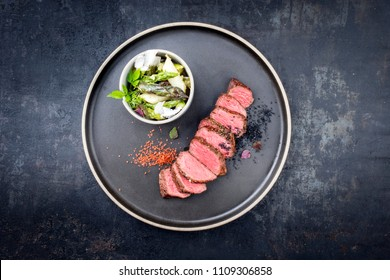 Modern barbecue dry aged sliced fillet steak spring salad with and green and white asparagus as closeup on a plate copy space