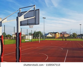 Modern basketball court in the courtyard of primary school. Multifunctional children's playground with artificial surfaced fenced with mesh fence.Place of physical education of children and young.