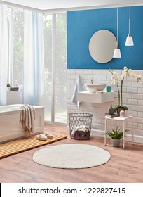 Modern bath room decoration. Sink and tub in the room. Blue and ceramic wall. Towel, mirror, lamp and blue cabinet in the bath room.