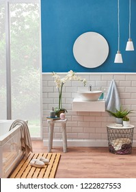 Modern bath room sink detail with blue wall and ceramic style. Decorative mirror and lamp in the room and white tub with wooden we floor. Slipper towel object in the bath room.