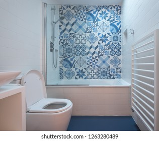 Modern bathroom with bath, toilet, niche in wall and basin unit, blue rubber floor and blue and white patchwork tiles above the bath.