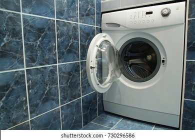 Modern bathroom with blue tiles  and washing machine