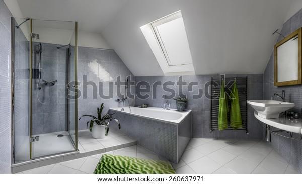 Phòng tắm hiện đại theo phong cách mát mẻ với vòi sen thủy tinh và bồn tắm trong gác mái của một ngôi nhà