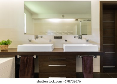 Modern bathroom with dark brown furniture, white sinks and towels