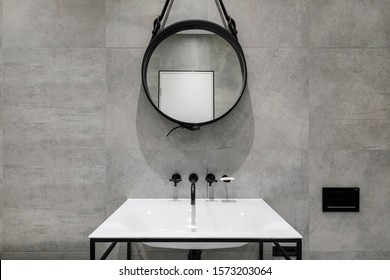 modern bathroom detail in neutral colours with black fixtures and round mirror