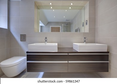 modern bathroom detail with twin sinks. built-in cupboard and large mirror in natural looking hdr image