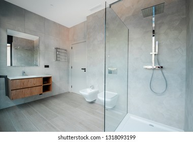 Modern bathroom with a glass bathtub and luxury washbasin. The walls and floor are covered with modern tiles.