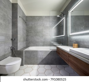 Modern bathroom with gray and white tiles. There is a large mirror with luminous lamps, tabletop with wooden drawers and sink, bath with shower and a glass partition, towel rack and a white toilet.