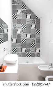 Modern bathroom with high ceiling, walk in shower and black and white monochrome porcelain wall tiles.